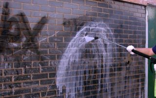 Graffitifjerning med  hjelp av fasaderengjøring. Foto